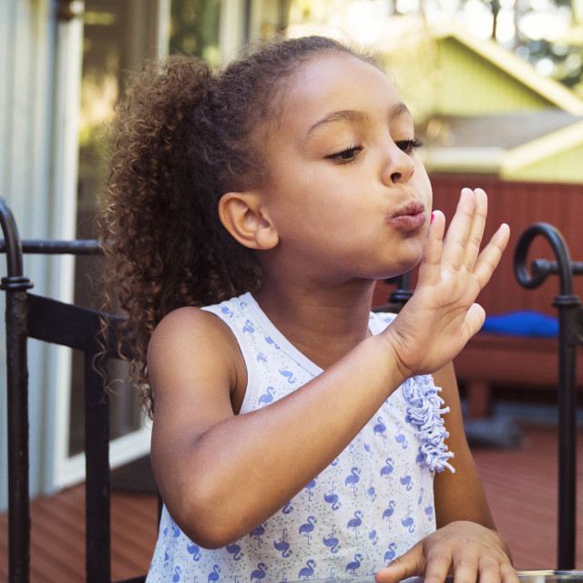 """""""Girl blowing nail polish on fingernails while sitting at table in yard"""" stock image"""