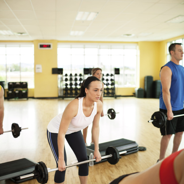 """Determined athletes lifting barbells by steps in gym"" stock image"