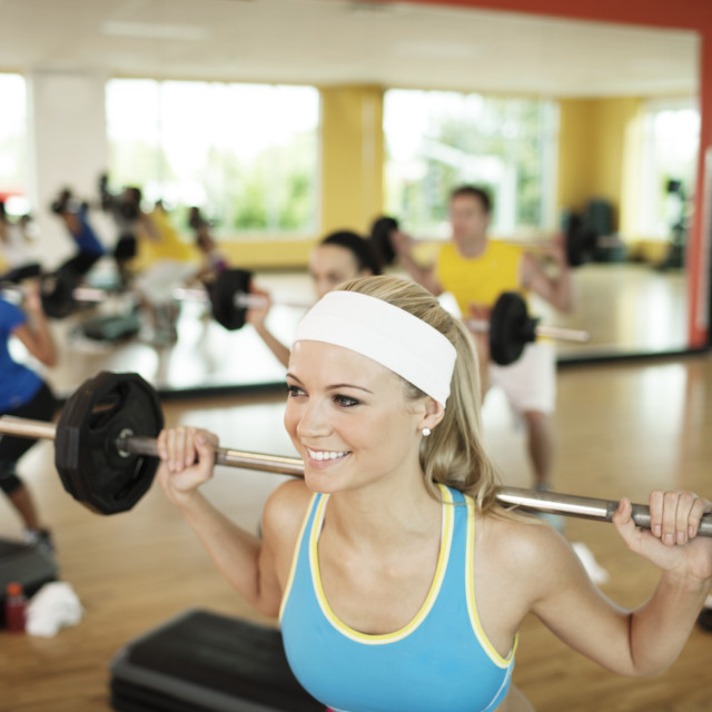 """Happy woman lifting barbell in gym"" stock image"