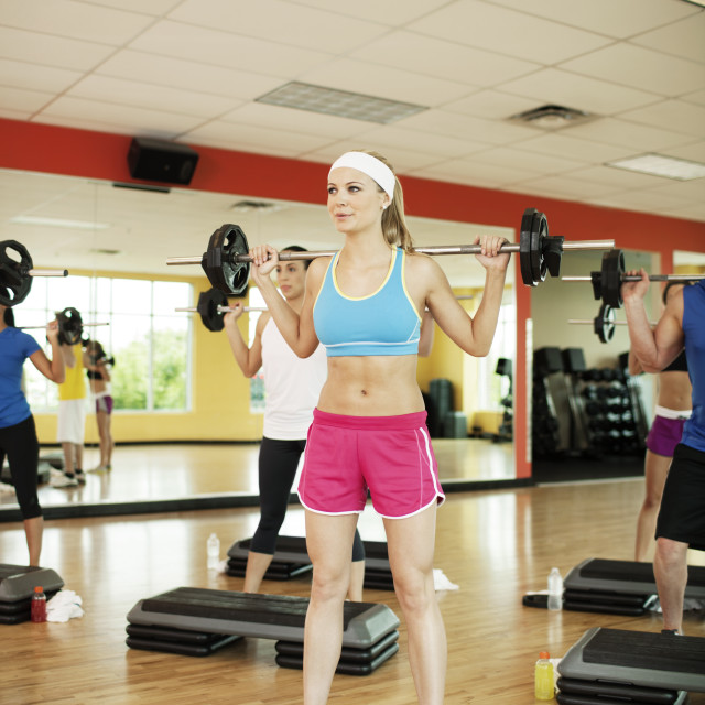 """Determined athletes lifting barbells by steps in health club"" stock image"