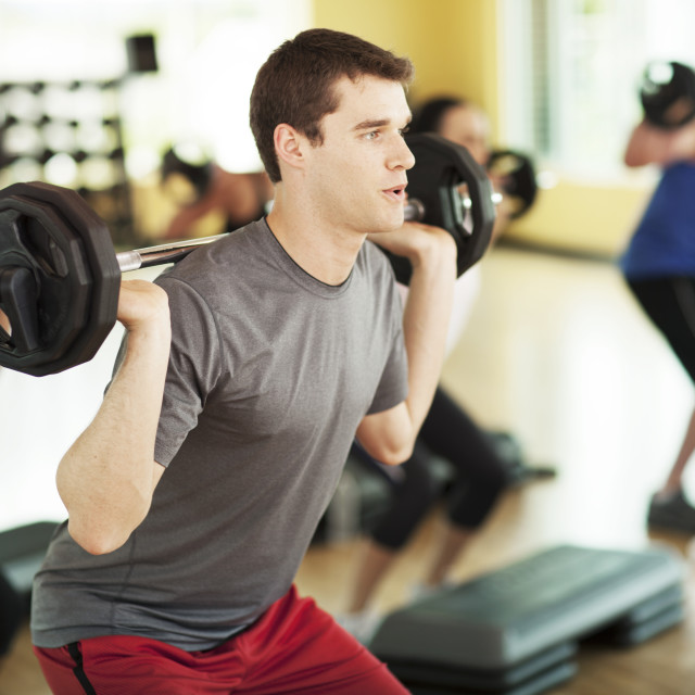 """Male athlete lifting barbell in gym"" stock image"
