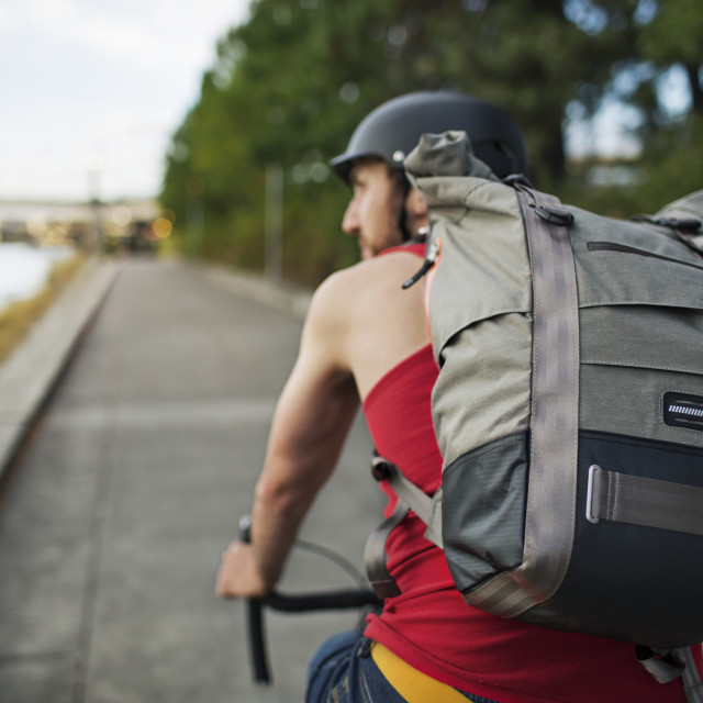 """Man carrying backpack while riding bicycle on street"" stock image"