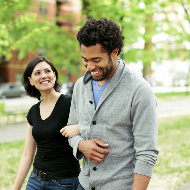 """Cheerful multi-ethnic couple walking in park"" stock image"