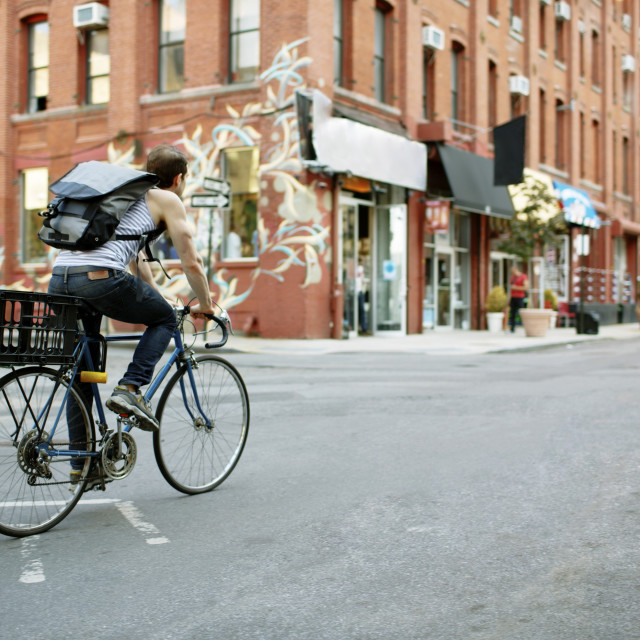 """Man with backpack riding bicycle on city street"" stock image"