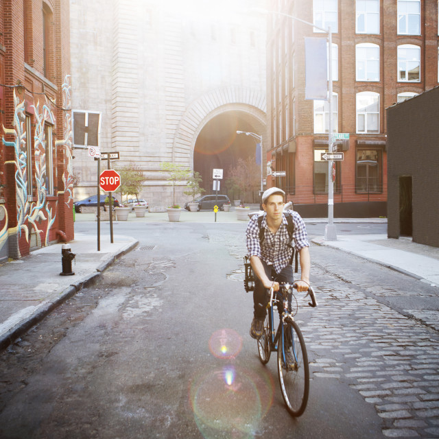"""Man riding bicycle on street amidst buildings"" stock image"