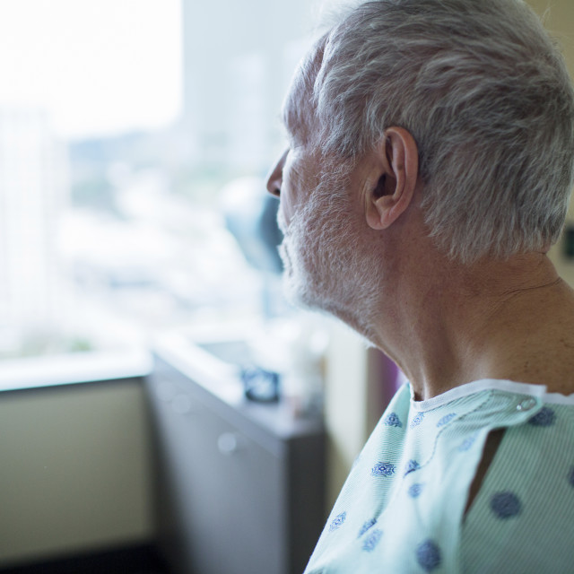 """Close-up of patient looking away while relaxing in hospital ward"" stock image"