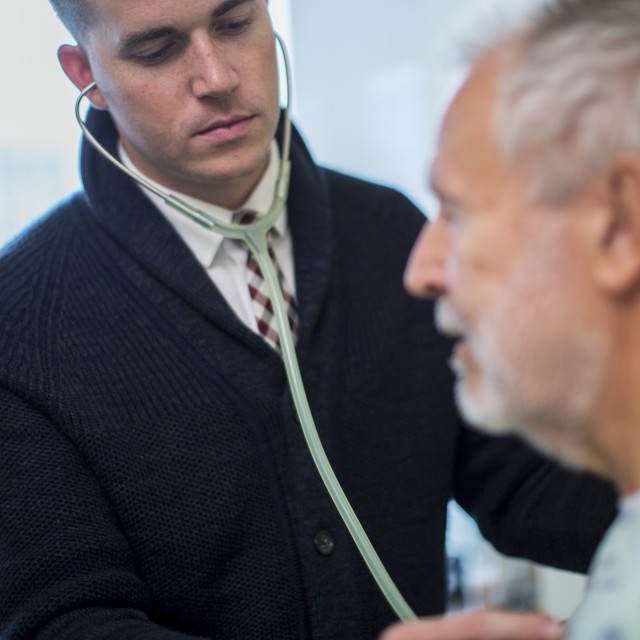 """Male doctor listening to patient's breathing in hospital ward"" stock image"