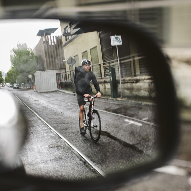 """""""Male commuter riding bicycle on wet street seen through side-view mirror of car"""" stock image"""