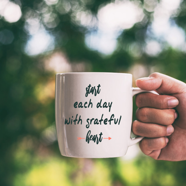 """""""Hands holding cup of coffee with quotes - Start each day with grateful heart."""" stock image"""