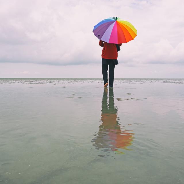 """Lone woman at the beach with colorful umbrella, Sasaran beach, Kuala Selangor, Malaysia."" stock image"