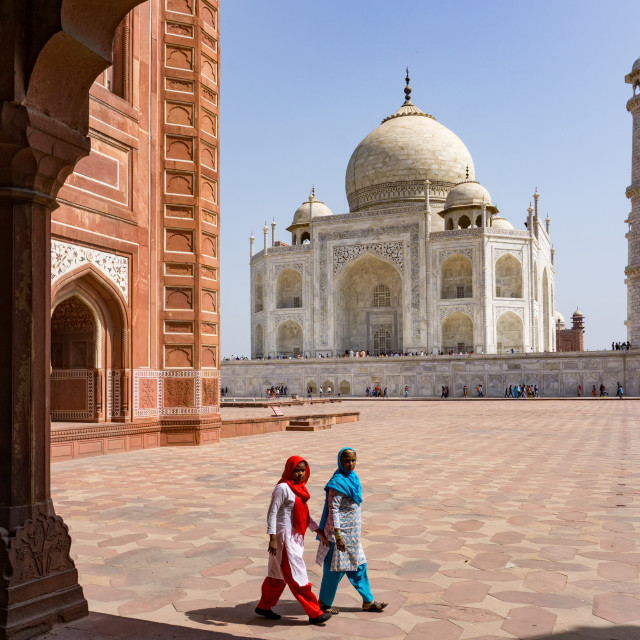 """""""Two Indian women at Taj Mahal. The Taj Mahal is an ivory-white marble mausoleum and most popular landmark in India."""" stock image"""