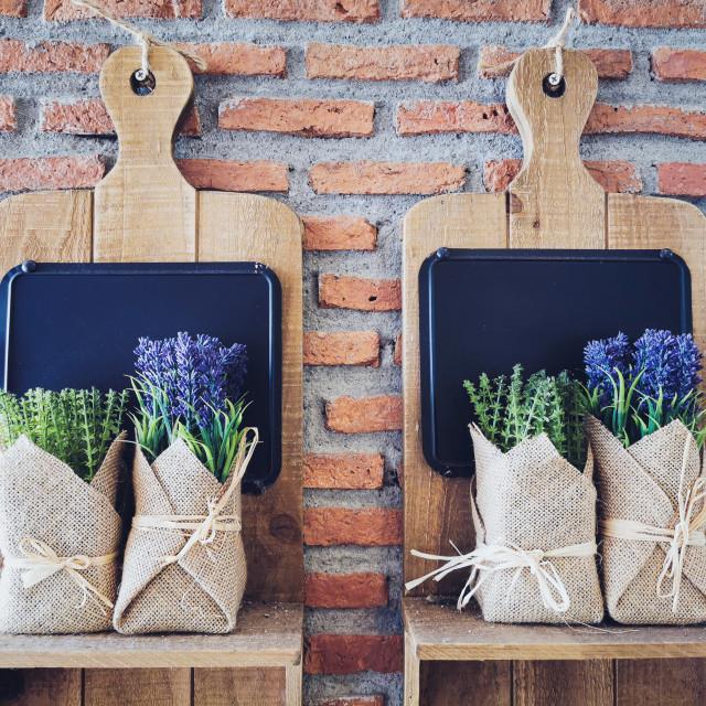 """fake purple flowers on wooden shelf"" stock image"