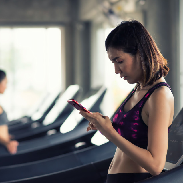 """""""woman play smartphone after workout in gym"""" stock image"""