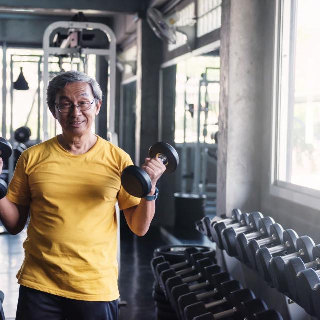 """Senior strong man dumbbell exercise in gym"" stock image"