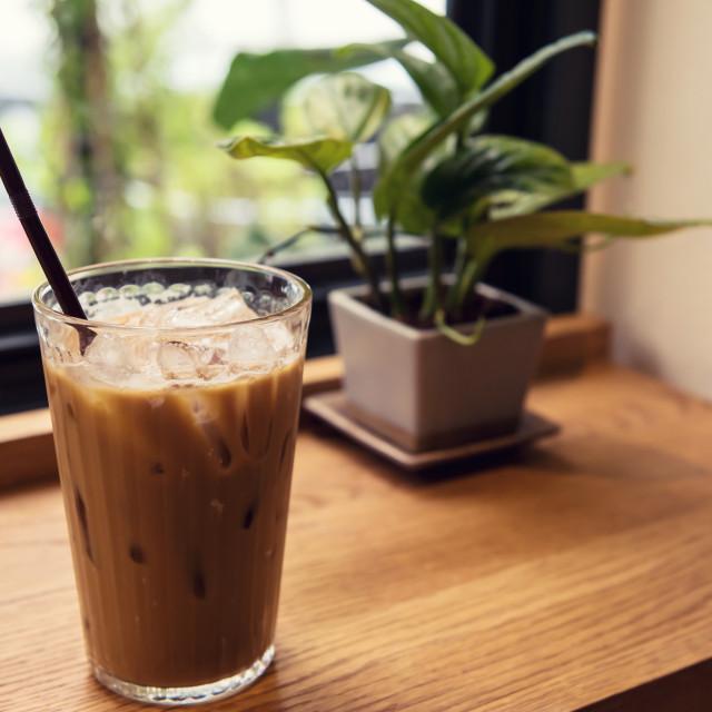 """Ice coffee on wood table near window"" stock image"