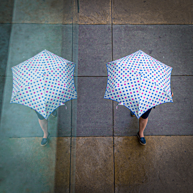 """Reflection of a woman with an umbrella"" stock image"