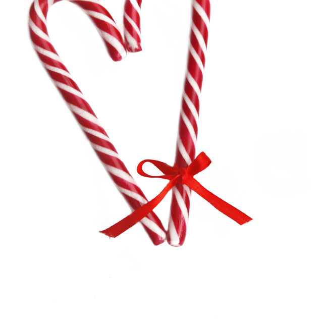 """""""candy canes forming a heart with a little ribbon on one and isolated on white"""" stock image"""