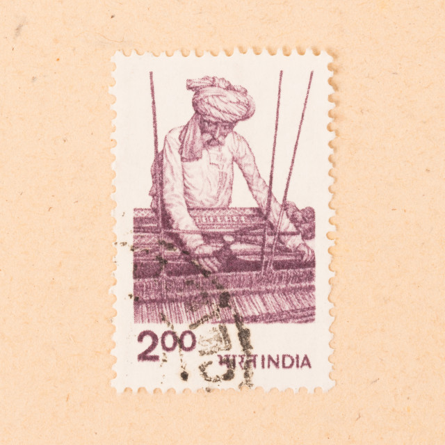"""""""INDIA - CIRCA 1970: A stamp printed in India shows a man working a loom,..."""" stock image"""