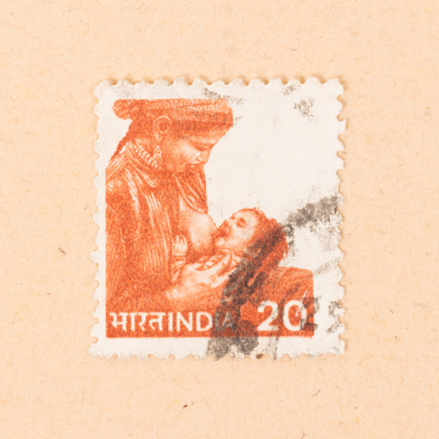 """""""INDIA - CIRCA 1970: A stamp printed in India shows a woman breastfeeding a..."""" stock image"""