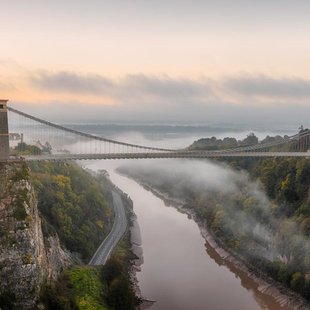 """Mist moving down the Avon Gorge at sunrise, going under Brunel's Clifton Suspension Bridge"" stock image"