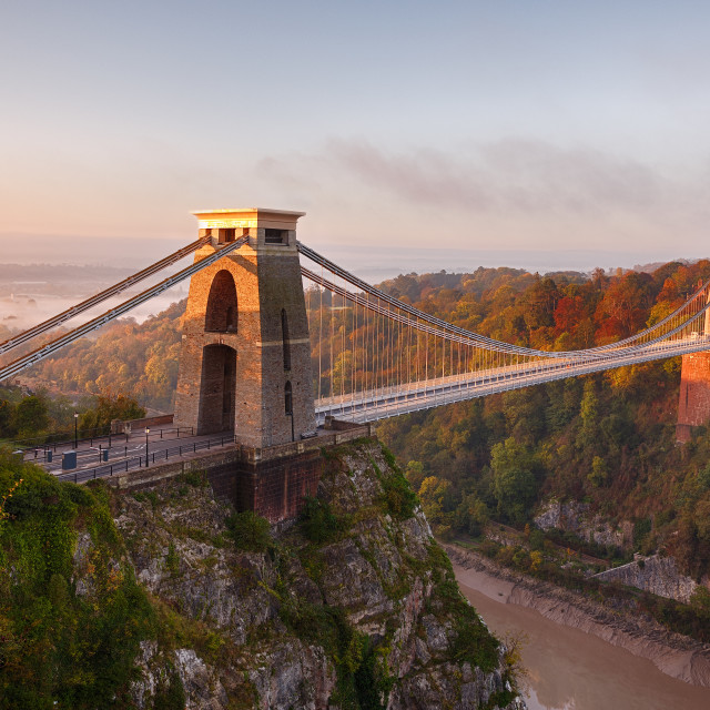 """""""Clifton Suspension Bridge on an autumn morning as the sun rises and breaks through the clouds"""" stock image"""
