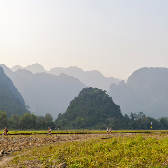 """""""People hiking and riding bike outside Vang Vieng"""" stock image"""
