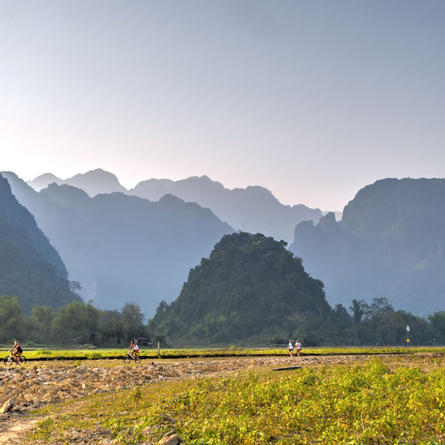 """People hiking and riding bike outside Vang Vieng"" stock image"