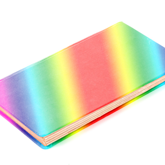 """Closed old rainbow colored book isolated"" stock image"