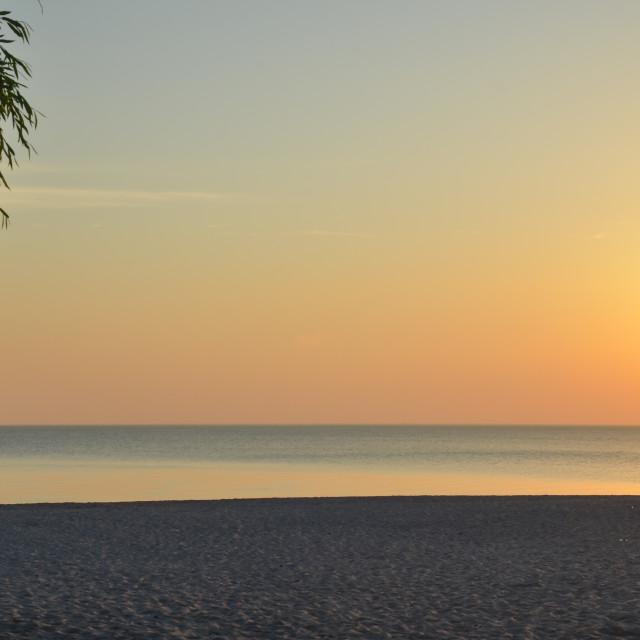 """Sunset by a beautiful empty sand beach"" stock image"