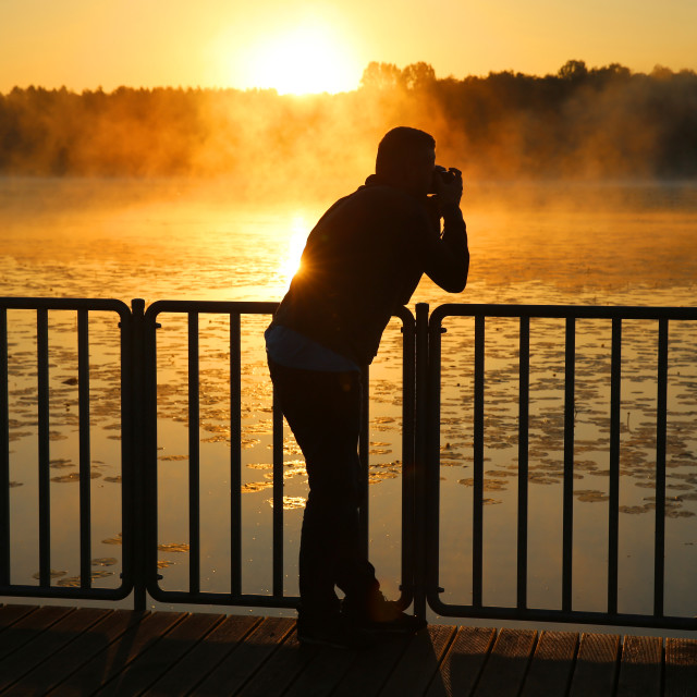 """A young man photographing the sunrise over a lake in Poland"" stock image"