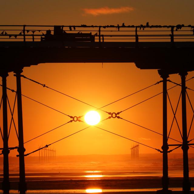 """Sun setting through Saltburn Pier"" stock image"