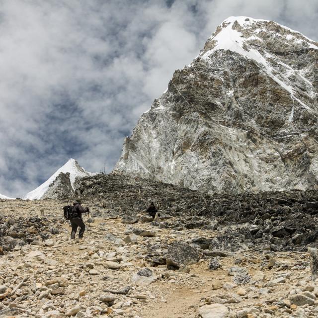 """Trekkers climbing Kala Patthar with Pumori high above them"" stock image"