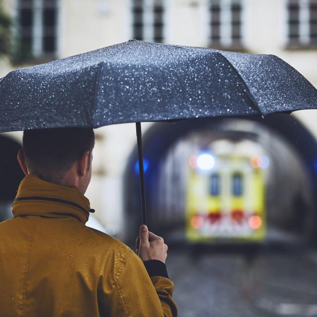 """""""Man with umbrella looking at leaving ambulance car"""" stock image"""