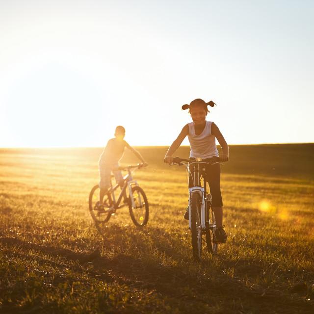 """Girl and boy enjoying bike ride"" stock image"