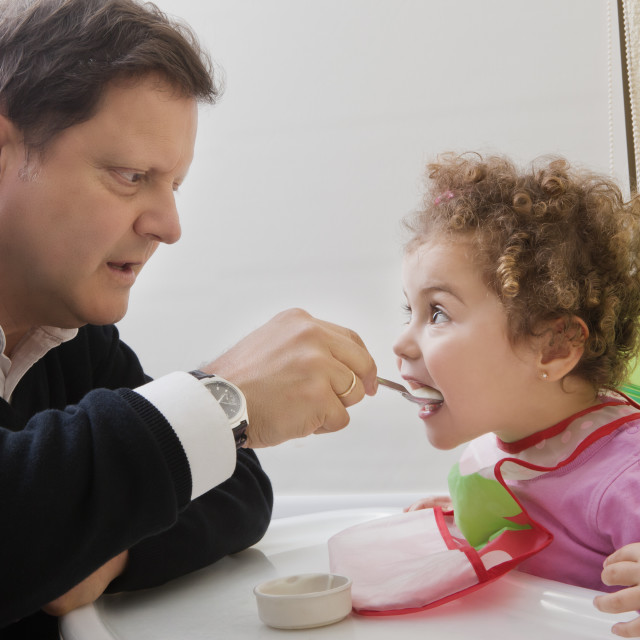 """Father feeding his daughter"" stock image"