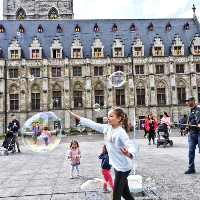"""Children chasing bubbles in front of the Stadhuis, Gent"" stock image"