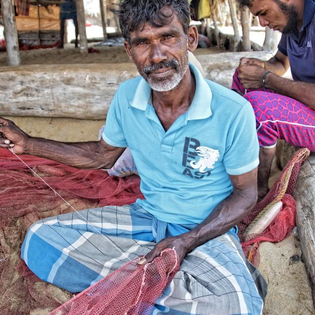 """Kiriba - a Sri Lankan fisherman mending nets near Dolphin Bay"" stock image"