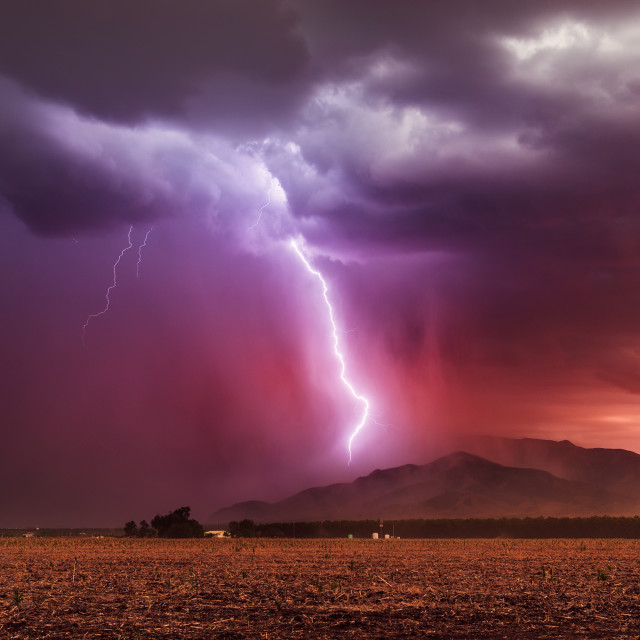 """Lightning bolt striking a mountain during a storm at sunset"" stock image"