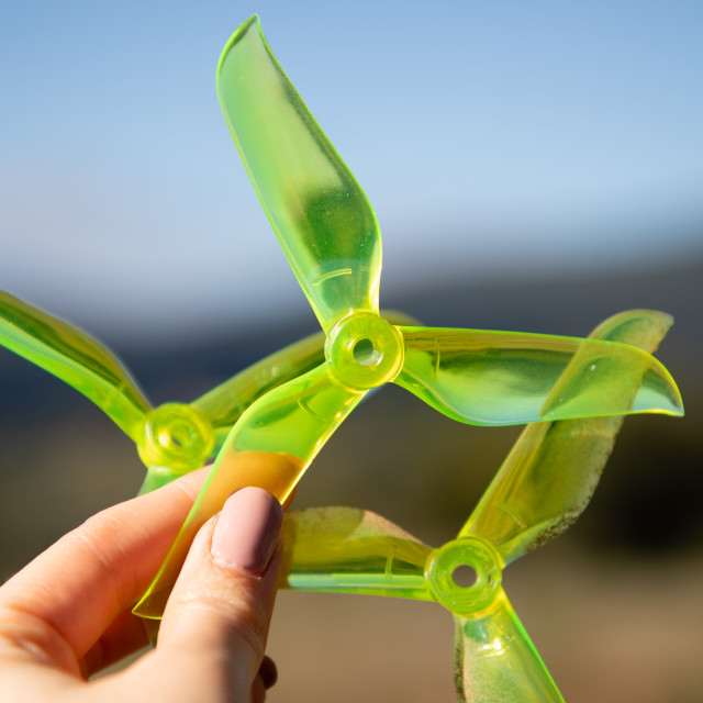 """Hand holding green racing drone propellers"" stock image"