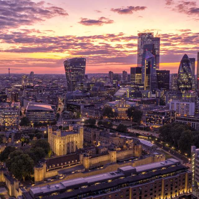 """""""The summer sun sets over the City of London. Built by William the Conquerer in 1078 The Tower Of London stands like a island against the futuristic skyscrapers of 21st century London. The country is set to enjoy the hottest spell of the summer so far with"""" stock image"""