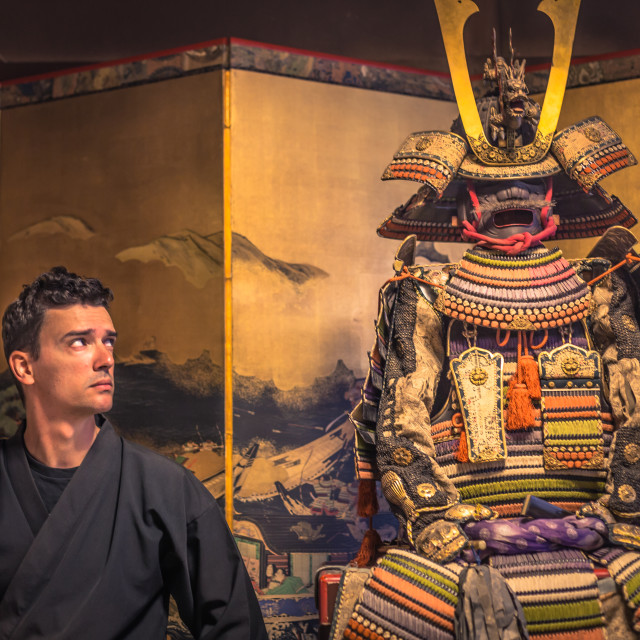 """""""Kyoto - May 29, 2019: Western traveler by the side of a Samurai armor in a..."""" stock image"""