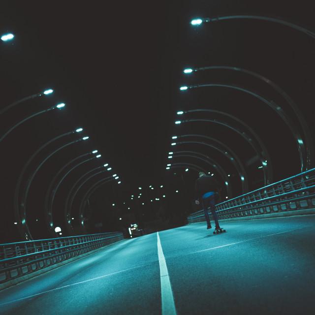 """Angled shot of a skater on a road at night. Valmieras bridge, Valmiera, Latvia."" stock image"