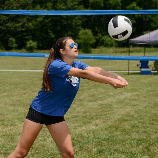 """Girl passing volleyball on grass court"" stock image"
