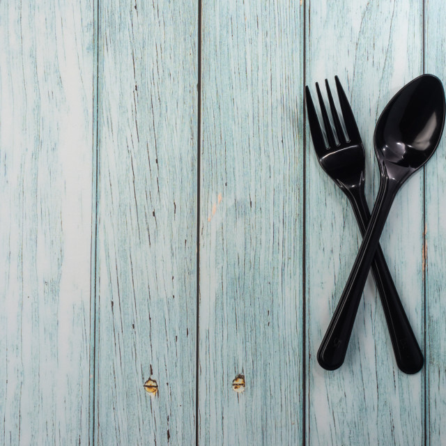 """""""Plastic Spoon and Fork on wooden background. Negative space"""" stock image"""