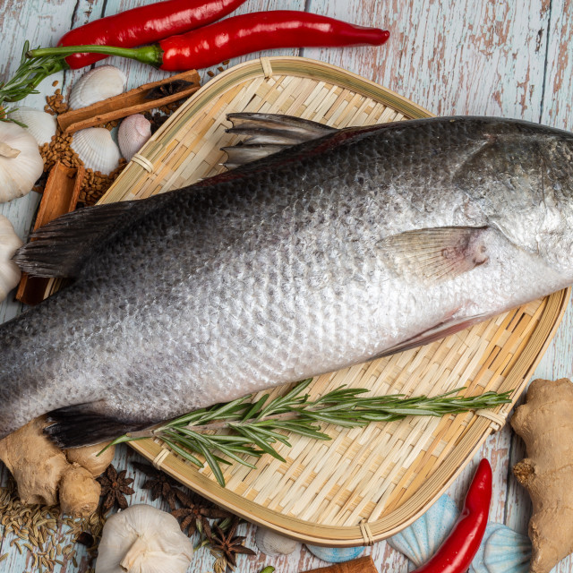 """""""Fresh Sea Bass on rattan plate and wooden background"""" stock image"""