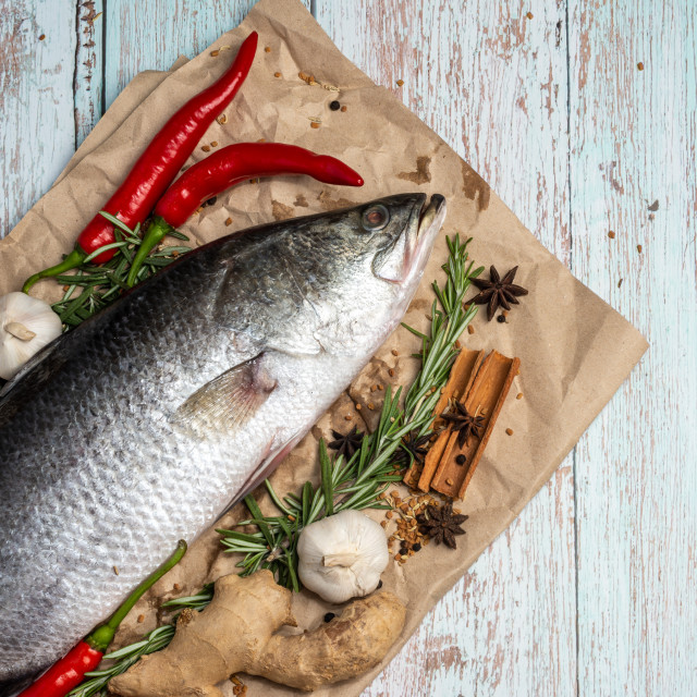 """""""Fresh Raw Sea Bass on wooden table surrounded by fresh ingredients and spices."""" stock image"""