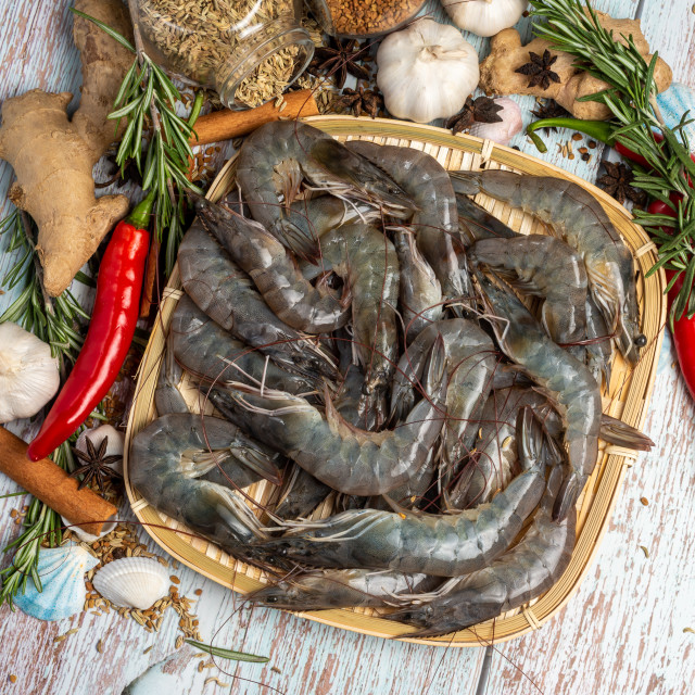 """""""Fresh Tiger Prawns on a rattan plate surrounded by fresh raw ingredients."""" stock image"""