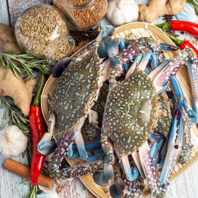"""""""Fresh Raw Crab surrounded by spices and ingredients on a wooden table"""" stock image"""