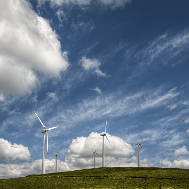 """Wind farm on a green hill under a blue sky"" stock image"