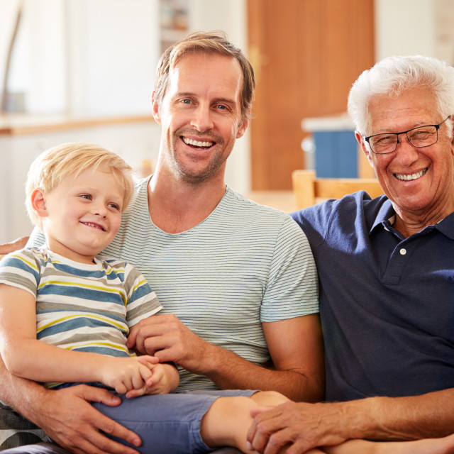 """Portrait Of Father With Adult Son And Teenage Grandson Relaxing On Sofa And..."" stock image"